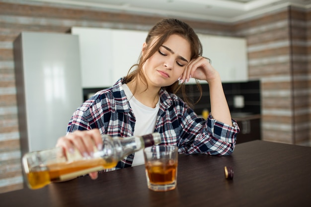 Female alcoholic has social problems sitting drinking whiskey. bored lonely woman pouring whiskey in glass.