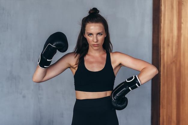 女性のアマチュアボクサーはボクシンググローブでポーズをとる。