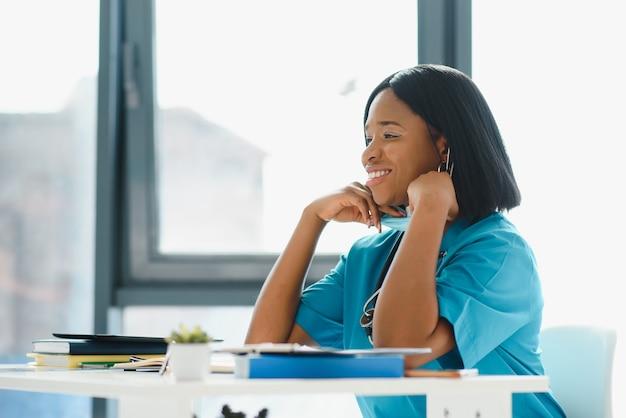 女性のアメリカのアフリカの医者、聴診器とマスクで医療コートを着ている看護婦。明るい背景でポーズをとる成功した医療従事者に満足しています。パンデミックの概念、covid 19