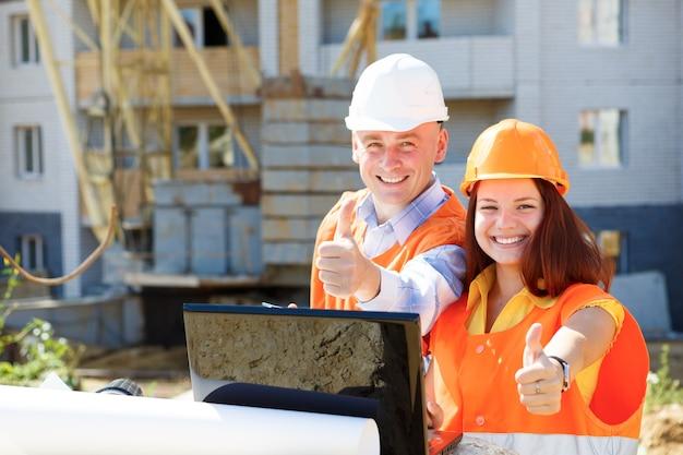 ノートパソコンを見て笑っている女性と男性の建設労働者