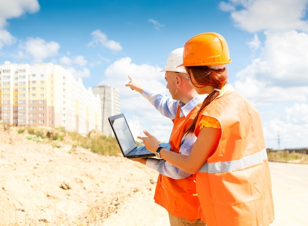 建設中の家のラップトップを見ている女性と男性の建設労働者