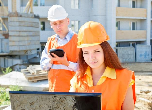ノートパソコンを見ている女性と男性の建設労働者