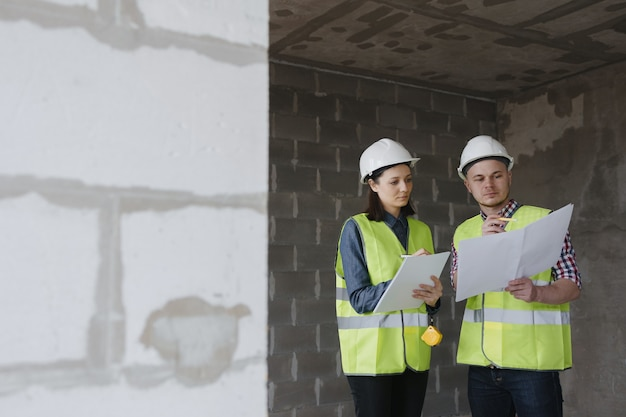 건설 현장에서 흰색 헬멧과 노란색 안전 조끼를 입은 여성 및 남성 엔지니어