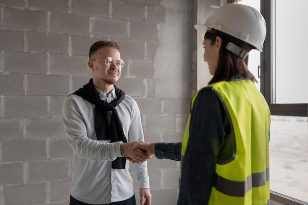 建設現場で白いヘルメットと黄色の安全ベストを着た女性と男性のエンジニア