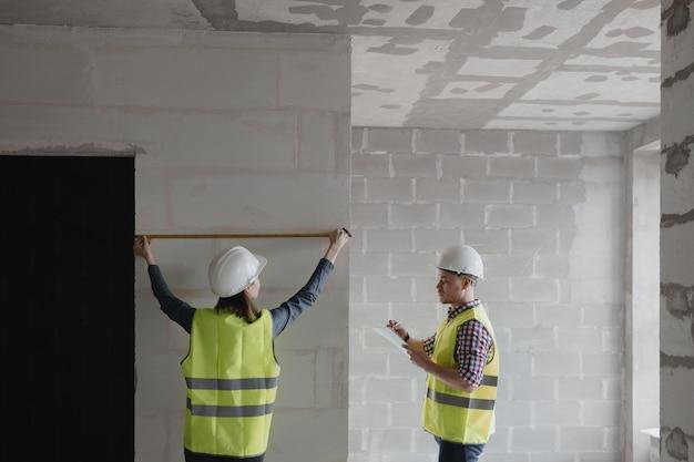 建設中の白いヘルメットと黄色の安全ベストの女性と男性のエンジニア
