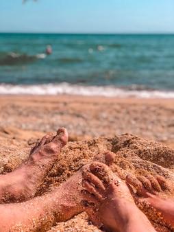 紺碧の海の水を背景に貝殻の砂浜のクローズアップの女性と男性の足。休暇と旅行のコンセプト。