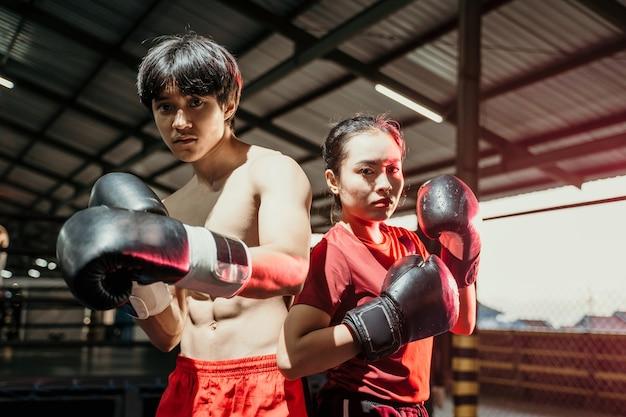 여성 및 남성 전투기는 권투 장갑에 서서 반지에서 등을 맞댄 포즈를 취합니다.