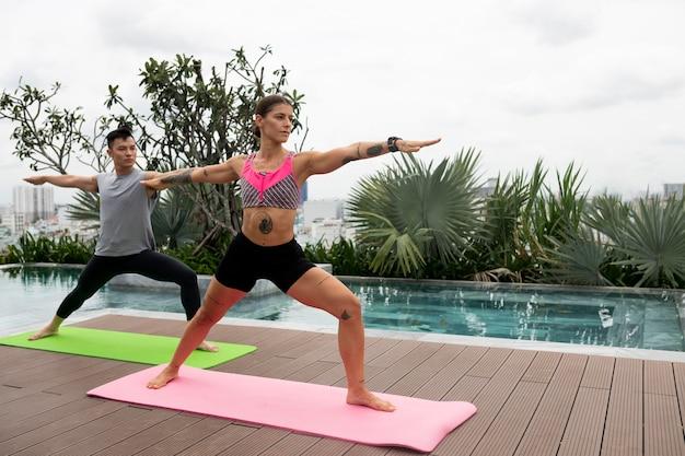 Друзья-женщины и мужчины практикуют йогу на коврике на открытом воздухе рядом с бассейном