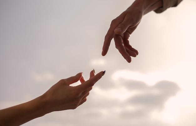 암컷과 수컷은 하늘 위로 손을 뻗는다. 도달, 도움의 손길, 서로 희망 및 지원의 실루엣