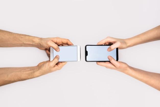 女性と男性の手がスマートフォンを持っています。メッセージング、テキストメッセージ、コミュニケーションの概念