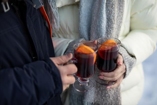 ホットワインのグラスを保持している女性と男性の手