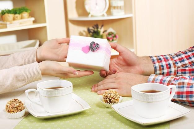 Женские и мужские руки с чашками чая и подарочной коробкой в домашнем интерьере