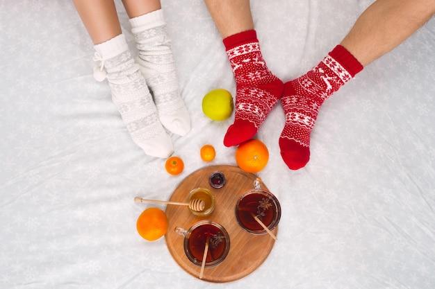 暖かいウールの靴下でカップルの女性と男性の足。冬の要素