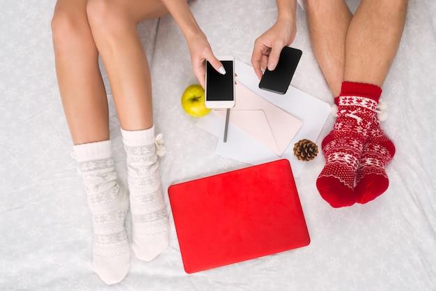ノートパソコンとスマートフォンで暖かいウールの靴下を履いたカップルの女性と男性の足。冬の要素