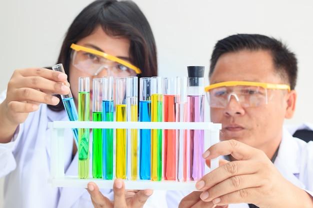 Женская и мужская команда ученых, изучающих цветную пробирку