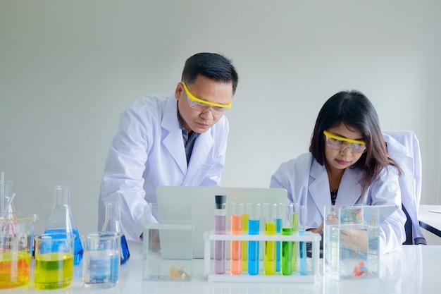 Женский и мужской ученый, работающий с ноутбуком и планшетом