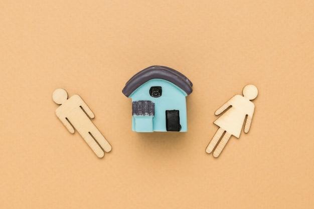 女性と男性の木製の置物とベージュの背景の家のモデル。