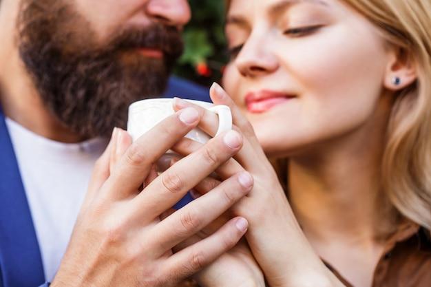 一杯のコーヒーを保持している女性と男性の手。コーヒーと手をつないで恋にカップル。コーヒーを楽しむカップル。手にコーヒーのカップを保持している素敵なカップル。あごひげを生やした男は女の子を抱きしめます。