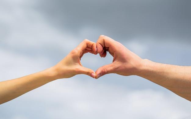 Женские и мужские руки в форме сердца на фоне неба. крупный план. сердце руки