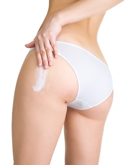 Female applying cosmetic cream from cellulite on leg