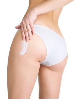 Женщина наносит косметический крем от целлюлита на ногу