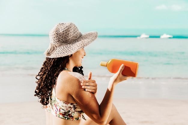 Женщина, применяя солнцезащитный крем на берегу моря