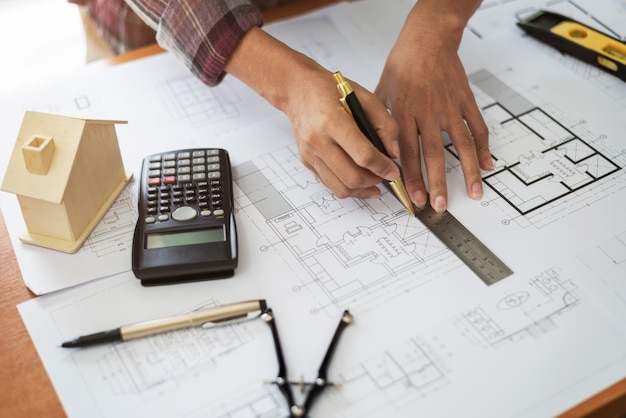 Female architect drawing blueprints in office workplace.