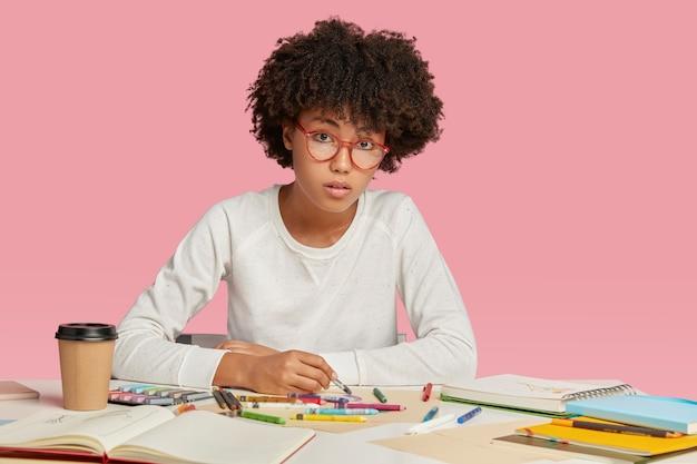 Женщина-архитектор имеет афро-прическу, работает над дизайном, рисует в блокноте картинки, смотрит серьезно, носит очки.