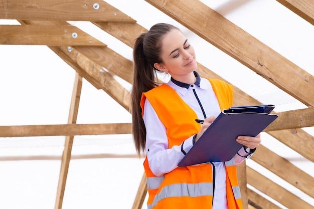 若い学生エンジニアが屋根の対策をチェックして注意する若い女性をクローズアップする場所を検査する女性建築家