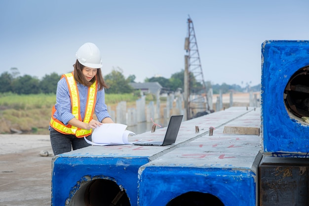 Female architect leader working with laptop and blueprints at construction site or building site.
