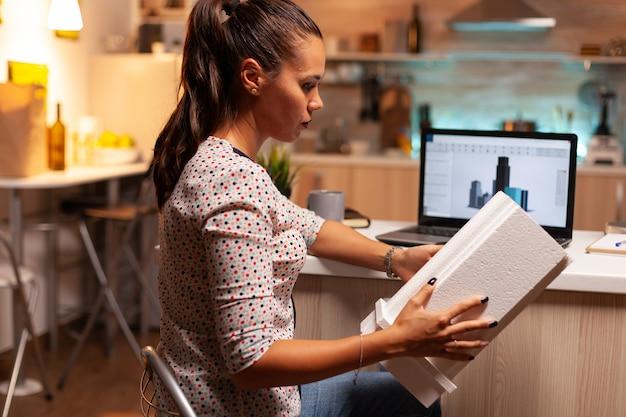 여성 건축가는 홈 오피스에서 늦은 밤 시간에 건물 모델을 보고 있습니다. 규모 건물 모델, 결단력, 경력을 들고 사무실에서 만들고 일하는 엔지니어 아티스트.