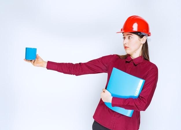 Architetto femminile in casco rosso documenti in mano tenendo il caffè.