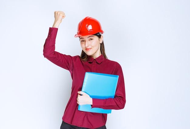 Architetto femminile in casco rosso che tiene cartella blu con documenti.