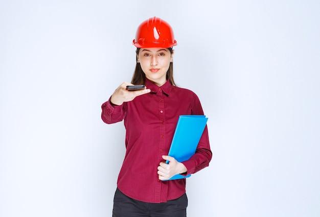 Architetto femminile in casco rosso che tiene appunti e dà via il cellulare.