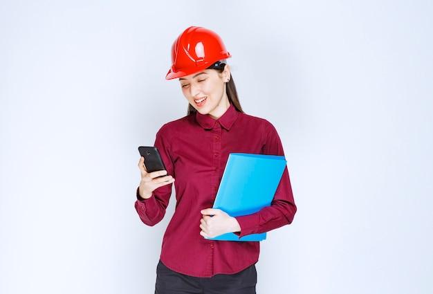 Architetto femminile in casco rosso che tiene appunti e parla tramite cellulare.