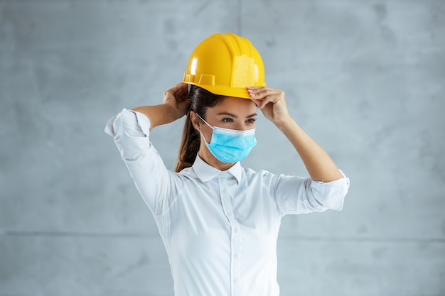 Female architect with face mask putting helmet on head