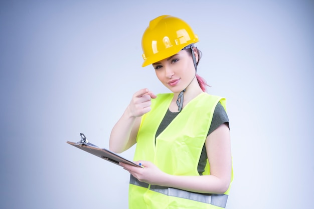 Female architect woman in a yellow helmet looks and points at front