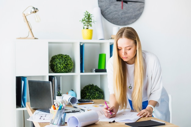 Female architect working on blueprint in office