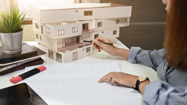Female architect working with model house and blueprint in home office.
