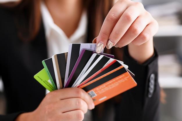 女性の腕はクレジットカードの束を保持します