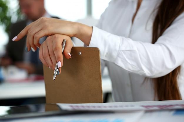 Женская рука в костюме держит серебряную ручку и блокнот