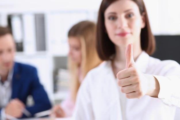 女性の腕はokまたは親指を上にして承認を示します