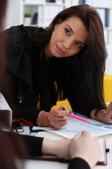 女性の腕は、オフィスのポートレートのパッドにクリップされた統計グラフィックを表示します。