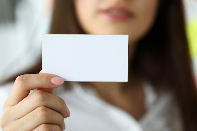 Female arm in suit give blank calling card to visitor
