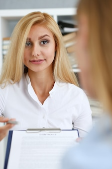 Female arm in white shirt offer contract form on clipboard