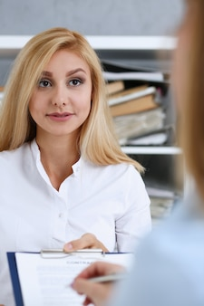 Female arm in white shirt offer contract form