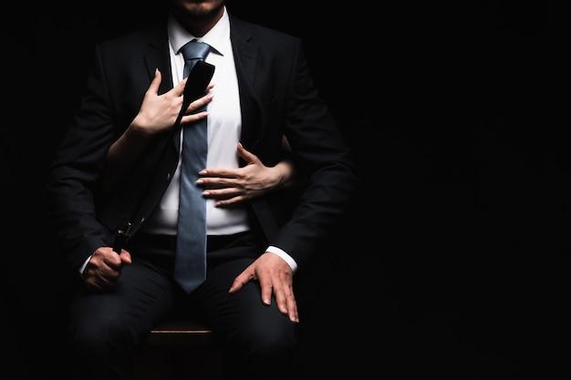 Женские руки обнимают доминанта-мужчину в костюме с кожаной плеткой флоггер. концепция бдсм секса с подчинением и доминированием