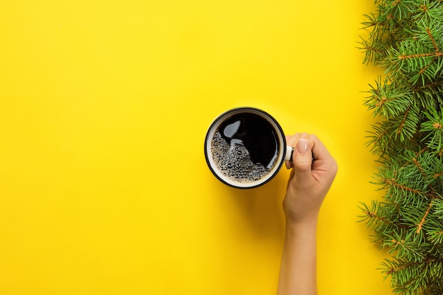Female arms hold mug of coffee on yellow background. top view with cope space