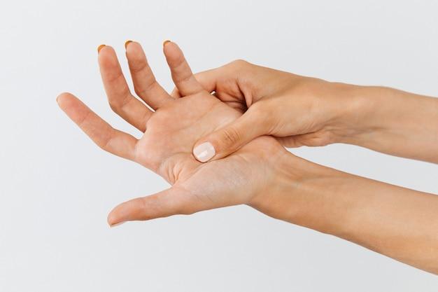 Женские руки держат ее болезненную ладонь, вызванную длительной работой за компьютером, ноутбуком. синдром карпального канала, артрит