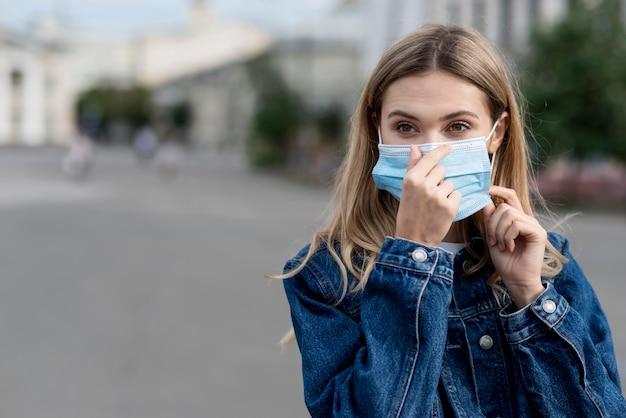 Женщина укладывает свою медицинскую маску для защиты